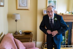 grandad fastens jacket for a tipi wedding in the peak district